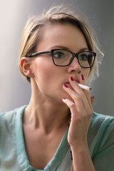 Young blonde woman smoking a cigarette outdoors.