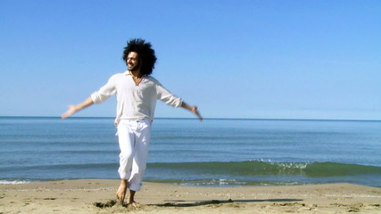 Handsome italian man dancing and jumping on beach slow motion