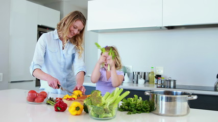 Smiling mother and daughter preparing a healthy dinner together