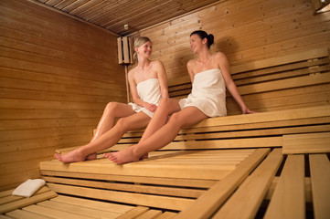 Two women chatting while relaxing at sauna