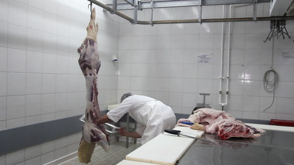 Butcher cutting pork meat with saw