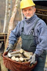 Mann mit Feuerholz Korb