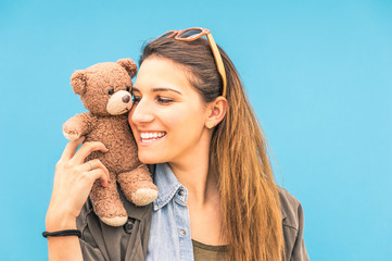 Young woman with teddy bear on her shoulder