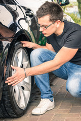 Young man inspecting car at second hand sale - Insurance concept