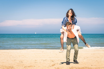 Young couple playing at the beach on piggyback jump
