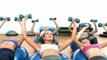 Fitness class lifting hand wieights on exercise balls