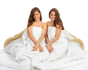 Twin sisters sitting on the bed