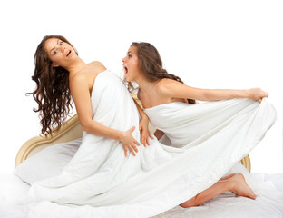 Twin sisters sitting on the bed and arguing on a white backgroun