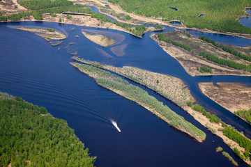 Top view of forest river with boat