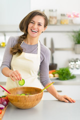 Happy young woman making salad in kitchen