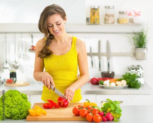 Szczęśliwa młoda kobieta ciie świeżych warzywa w kuchni