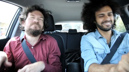 Two men sing and dance in car crazy
