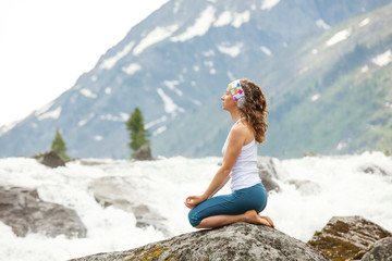 Young woman is practicing yoga at mountain river