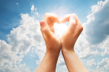 Man and woman hands make a heart on blue sunny sky. Love