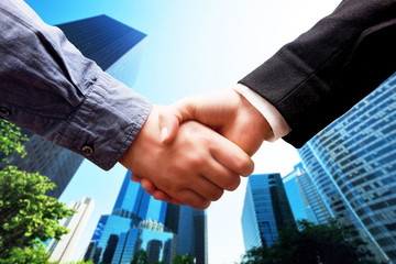 Business handshake, skyscrapers background. Deal, cooperation