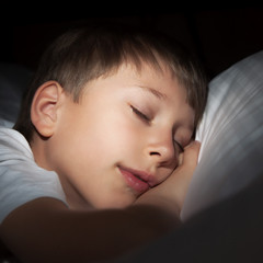 Beautiful little boy sleeping peacefully in bed smiling