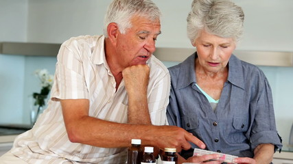 Senior couple organizing their medicine for the week