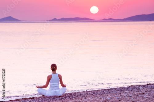 Caucasian woman practicing yoga at seashore - 64723227