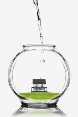 Water pouring on a house in a fishbowl