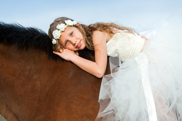 Portrait of cute girl laying on horseback.