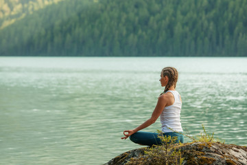 Young woman is practicing yoga at mountain lake