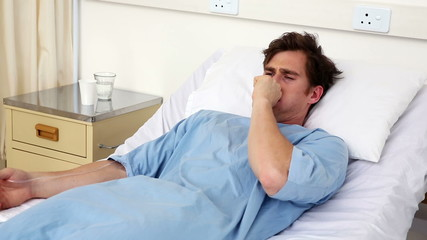 Sick man lying on hospital bed coughing