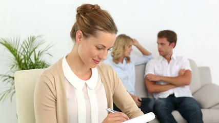 Couple talking on couch behind their therapist