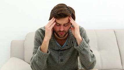 Young depressed man sitting on sofa