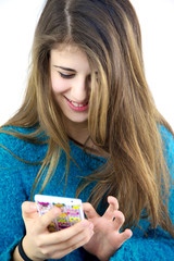 Happy female teenager playing with cell phone texting