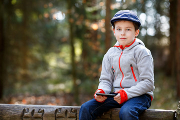 Portrait of little boy sitting on a bench outdoors