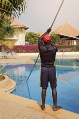 homme africain nettoyant piscine