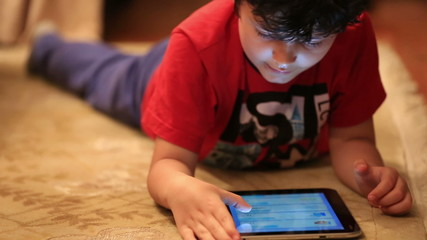 little cute kid playing digital tablet in home