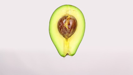 Oil drops from a half cut avocado on a white background