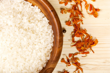 spices and rice in wooden bowl on  a wooden table background