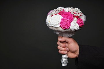Man holds at hand small wedding bouquet for bride
