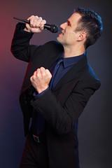 Karaoke with handsome man in suit on dark background