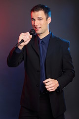 Handsome man in suit sings into the microphone