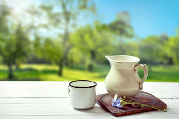 Milk jug and mug on sunny country background