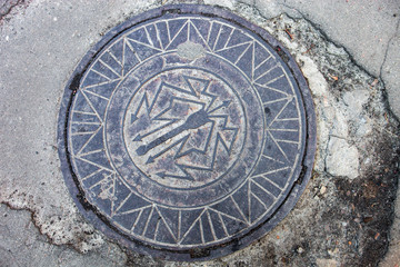 Manhole with metal cover in the cracked asphalt surface