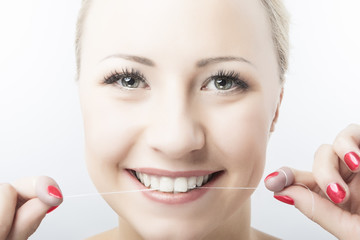 Caucasian Woman Flossing Teeth and Smiling. Dental Care and Oral