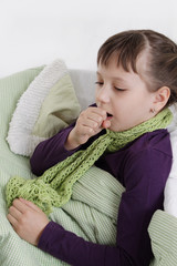 Girl coughs lying in bed with scarf