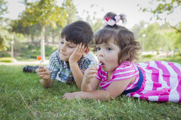 Young Brother and Baby Sister Enjoying Their Lollipops Outdoors