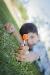 Young Boy Enjoying His Lollipop Outdoors Laying on Grass