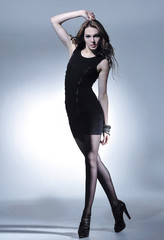 Full body sexy young woman in black dress on light background