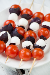 Kebabs with mozzarella, cherry tomatoes and purple basil