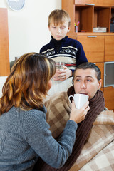 unwell man surrounded by caring wife and son