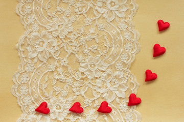 Beautiful lace on old paper with red satin hearts