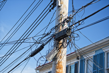 Electric cables tangle on wood post