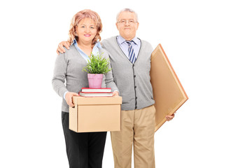 Mature couple posing with moving boxes