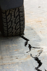 back view of tire tread and cracked asphalt